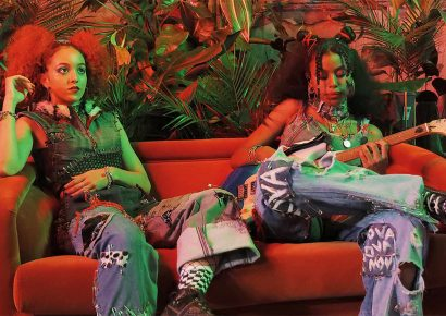 nova twins sitting on couch playing fender guitar